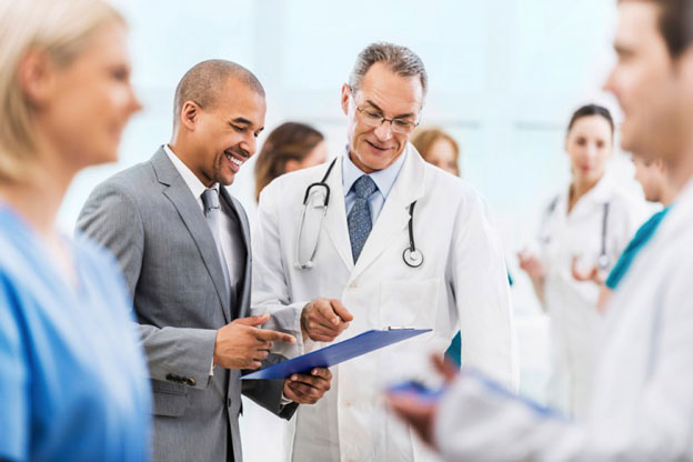 A picture in which several doctors are standing and discussing patient results with each other