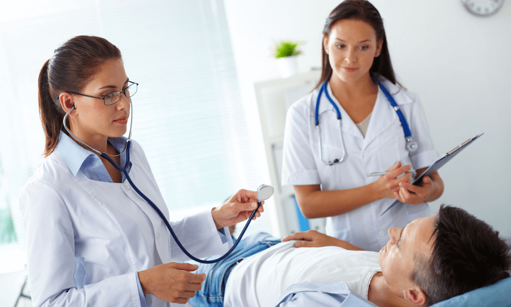 A patient is getting family practice treatment by two expert lady doctors