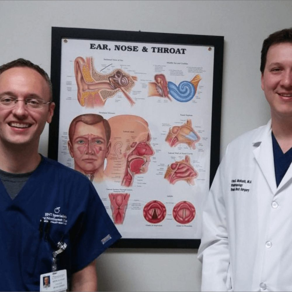 Two smilling doctors standing with a picture of Ear, Throat & Nose framed portrait on wall
