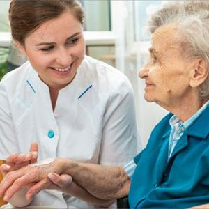 A young lady putting adhibiting lotion on old lady's hand for geriatic treratment