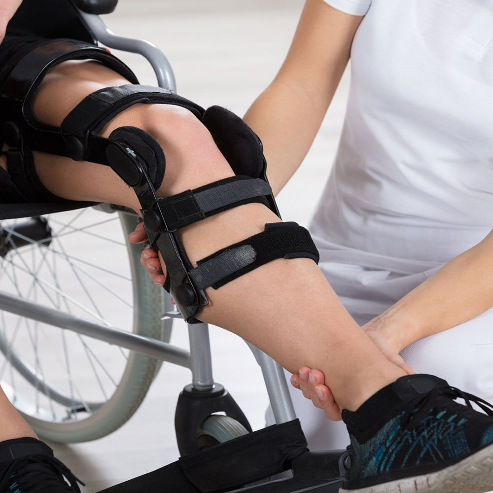 A female mmb specialist moving the leg of the patients afer he had ortho treatment from MMB