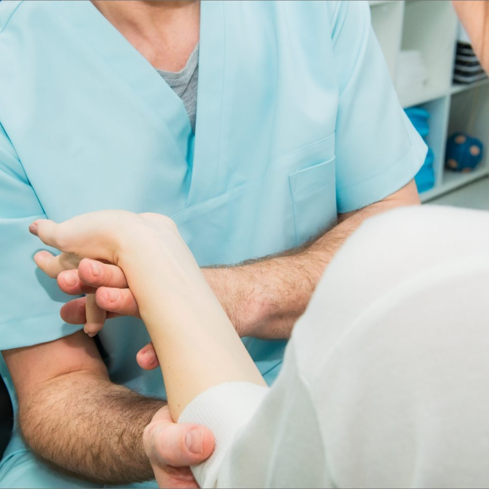 A doctor checking her patient's damaged wrist joint for treatment