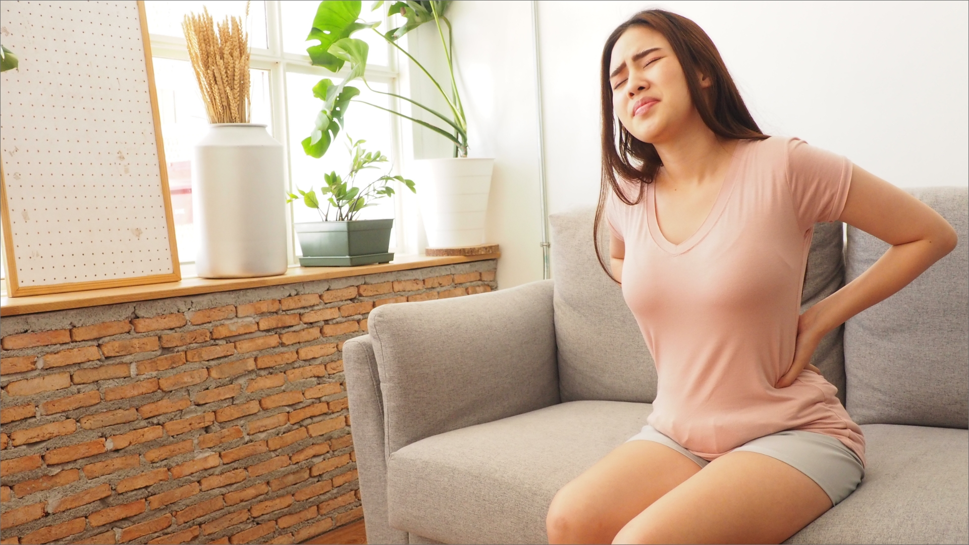 A lady stting on a sofa holding her back due to chronic back pain