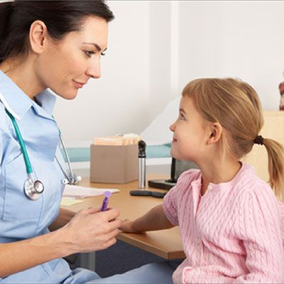 A lady doctor examining a child sitting with her mother for pediatrics (childern medicine)