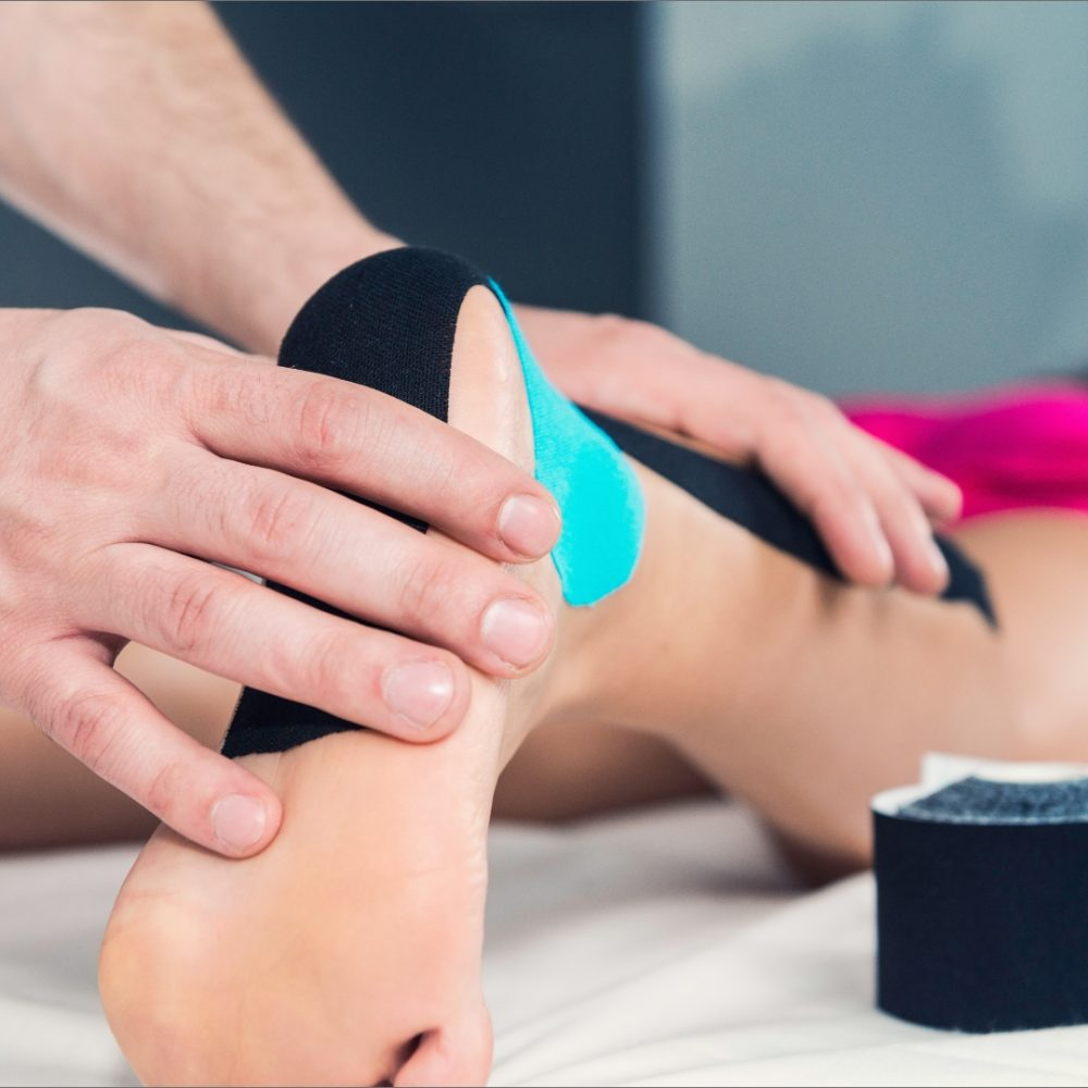 A chiropractor diganosing her lady patient's ankle with Kinesio Tape