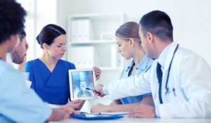 A female assistant is holding a tablet and a male doctor is giving a brief to the patient regarding spine