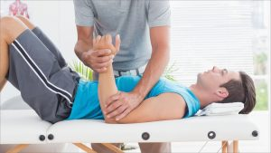 A fitness expert examining his sports paitent's arm movement to suggest sports medicine