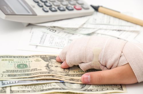 A calculator, pen and some cash is placed on a table and injured hand is identifing the ortho billing services