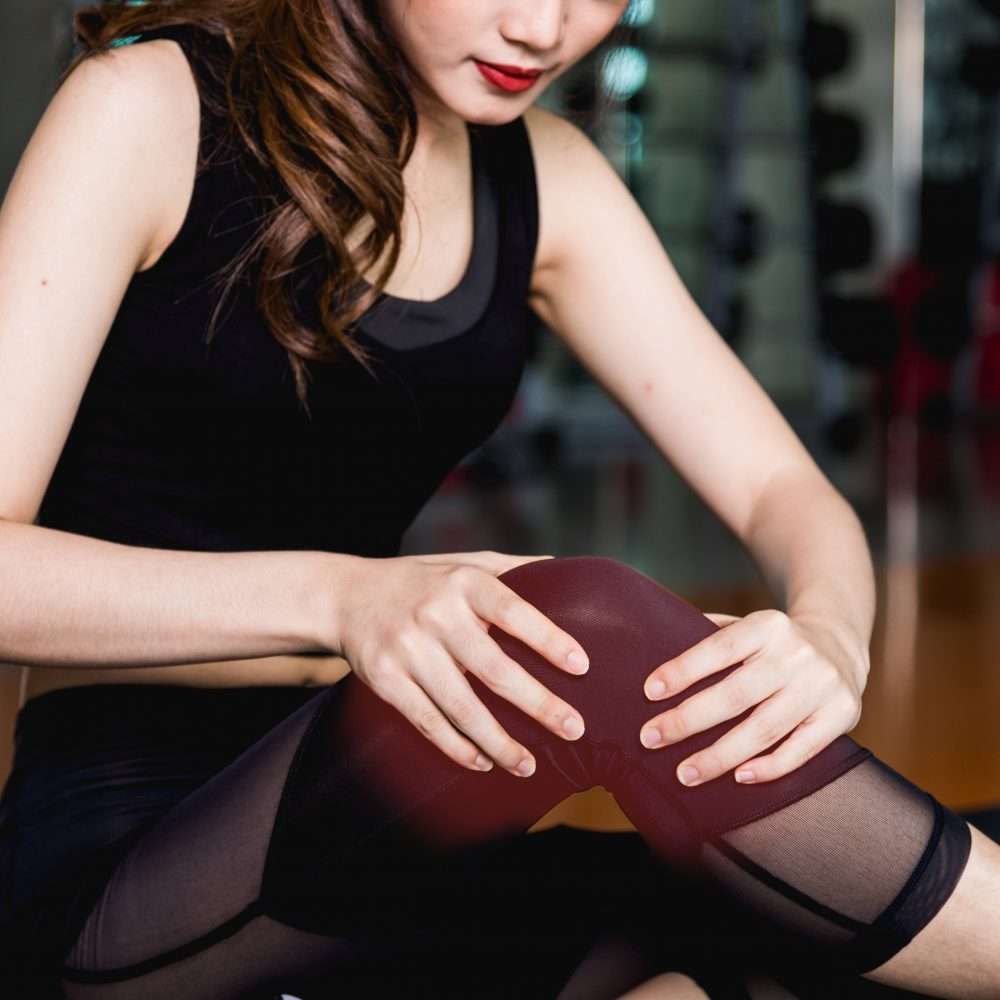 A lady holding her knee with both hands suffering form knee pain and wearing knee bracer