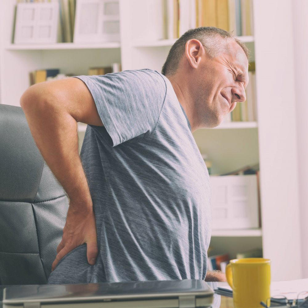 A man holding his back while sitting on a chair suffering from high back pain